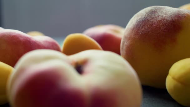 Apricots and peaches on dark texture surface. Close up of fresh summer fruits. 4k footage.