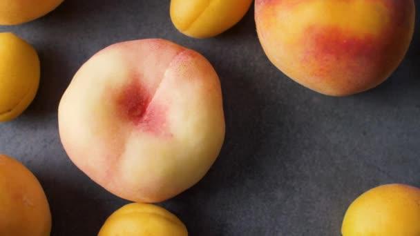 Sárgabarack és őszibarack a sötét textúra felületén. Közeli friss nyári gyümölcsök. Felülnézet. 4k felvételek.
