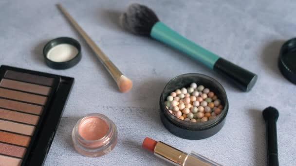 Ženská kosmetika se tvoří na povrchu stříbrného. Paleta a štětce se stíny očí s rozdílně barevnými pudry. 4k.