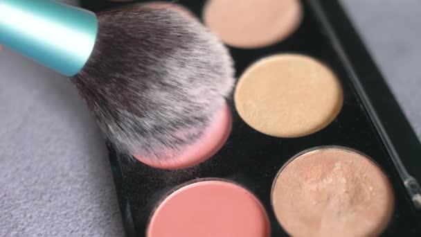 Paleta se stíny očí a štětcem na makeup v pomalém pohybu. Blízkka ženy tvoří kosmetiku s rozdílně práškovou barvou. 4k.