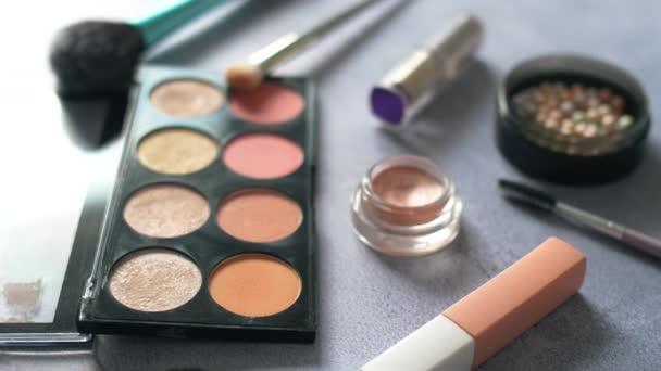 Ženská kosmetika dělá věci na povrchu textury. Paleta a štětce se stíny očí s rozdílně barevnými pudry. 4k.