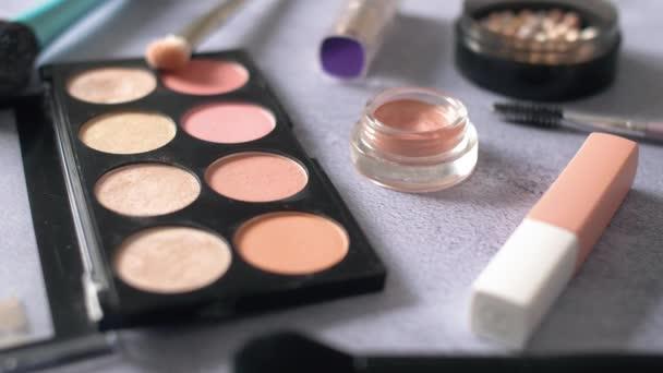 Női kozmetikumok teszik ki cucc a textúra felületre. Szemárnyékok palettát és kefék différents színes porok. 4k.
