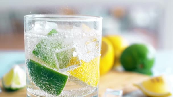 Close up of fresh summer drink with lime, lemon and ice cubes with bubbles mineral water. Slow motion footage.