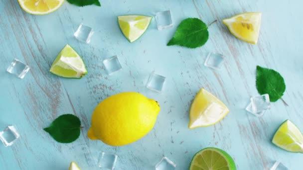 Uzavřete čerstvé krájené vápno a citrón s ledovými kostkami a zelenými listy na povrchu s modrým povrchem dřeva. 4 k citrusové plody v kuchyni. Pohled shora.