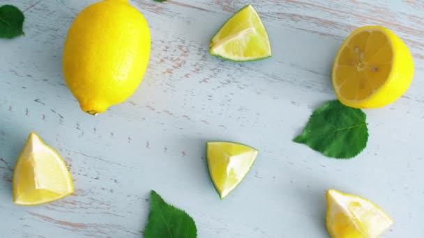 Közelről friss, szeletelt mész és citrom zöld levelei kék fából készült textúra felületén. 4k citrusfélék a konyhában.