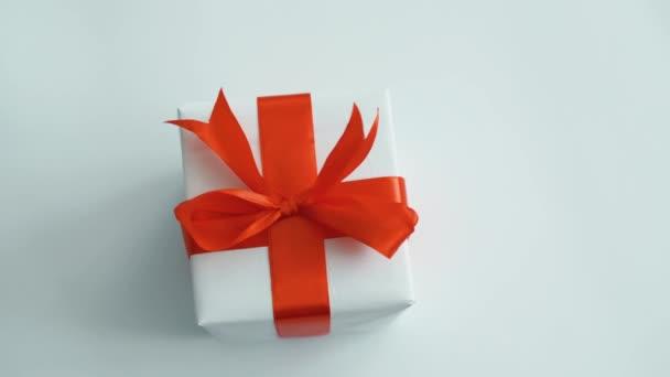 Bílá Dárková krabice s červeným hedvábným pásem. Dárková krabice pro Vánoce, černý pátek a další svátky. Zavřít 4k záběr.