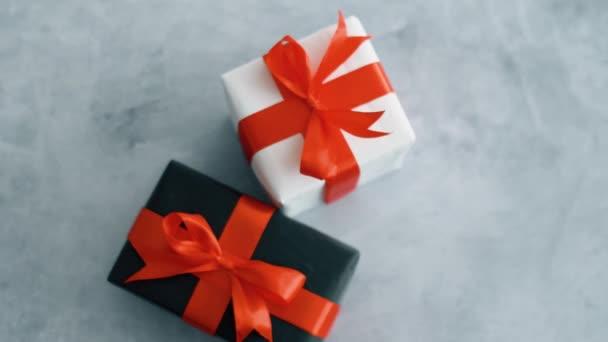 Černé a bílé dárkové krabice s červenou hedvábnou stuhou, otáčející se na povrchu šedé textury. Dárková krabice pro Vánoce, černý pátek a další svátky. Zavřít 4k záběr.