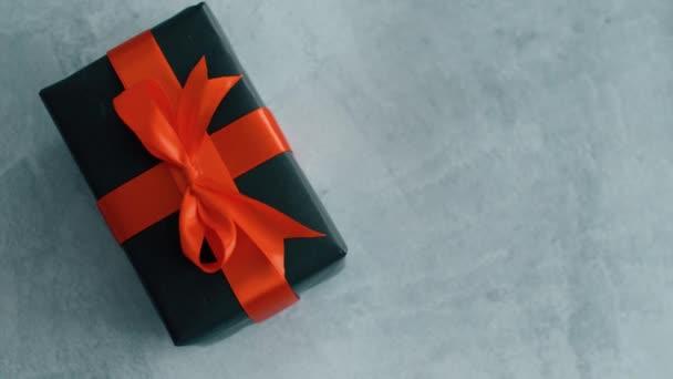 Černá Dárková krabice s červenou hedvábnou stuhou, otáčející se na povrchu textury. Dárková krabice pro Vánoce, černý pátek a další svátky. Zavřít 4k záběr.