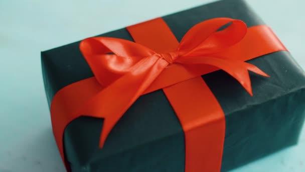 Černá Dárková krabice s červenou hedvábnou stuhou, která se otáčí na modré dřevěné struktuře. Dárková krabice pro Vánoce, černý pátek a další svátky. Zavřít 4k záběr.