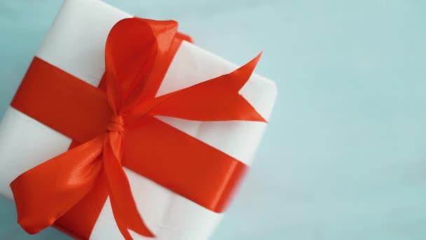 Fehér díszdobozban piros selyem szalag forgatható. Ajándékdoboz karácsonyra, fekete péntekig és egyéb ünnepek. 4k felvételek bezárása.