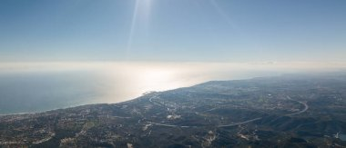 panoramic of two pictures together with a clear sky, the sea and the town of marbella