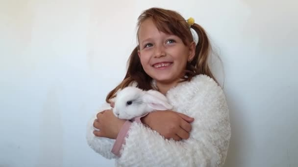 ein Mädchen hält ein weißes Kaninchen im Arm