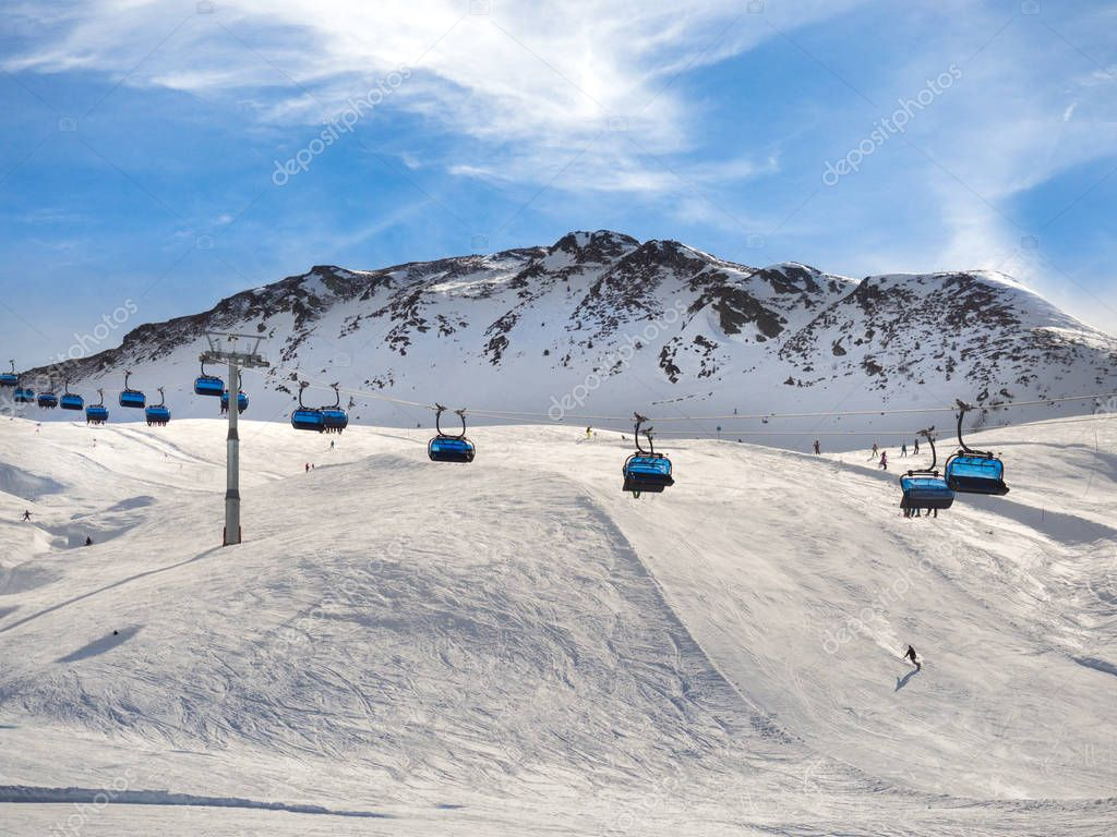 Chair lift transports skiers through the snow-capped mountains.