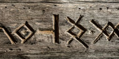 Ancient runes and hieroglyphs carved on a dry wooden board