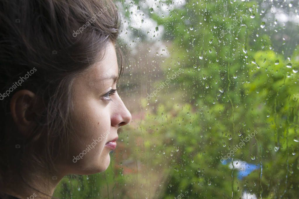 Sad girl looks out the window its raining. Woman with nice looking hear