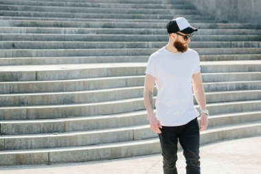 Hipster man walking wearing black jeans, t-shirt and a baseball cap