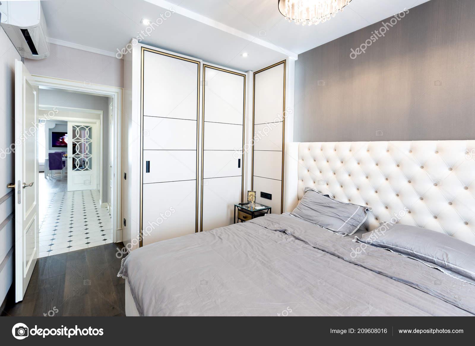 Moderne slaapkamer interieur met een groot bed een kroonluchter