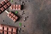 Vegane Bananenschokolade verziert mit Minzblättern und Schokoladenchips. Cremiger, milchfreier Eis-Pop. Dunkler Hintergrund