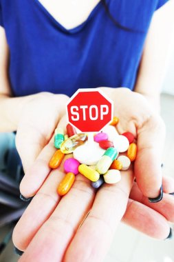 Stop antibiotics or medication excess with colorful pharmaceutical drugs in woman hand with stop sign on top