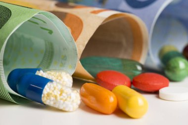 Macrophotography with colourful pharmaceutical drugs on rolled up euro banknotes