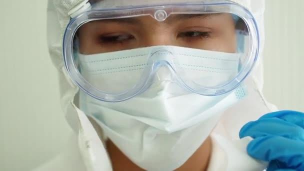 Ärztin oder Krankenschwester entfernt eine medizinische Maske und eine Schutzbrille. Müde Ärztin zieht medizinische Maske ab und wischt Schweiß mit der Hand von der Stirn.