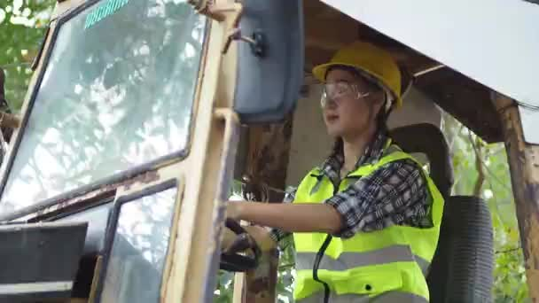 Žena krok nahoru do kabiny ovládání těžkého bagru, Mladá žena řidič sedí v kabině velkého moderního kamionu