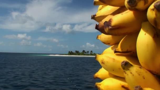 Világos sárga banán, háttérben a tenger víz felszínén a Maldív-szigetek