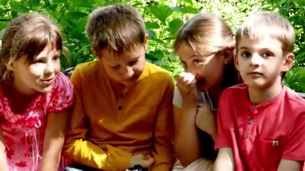 Děti s videokamerou na lavičce v pomalém pohybu zelený park.