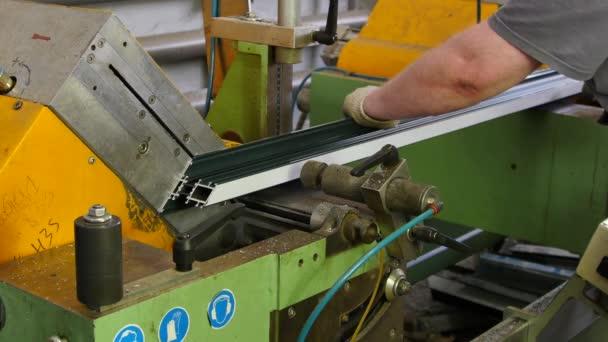 Pracovní ruce hliníkový profil s kotoučovou pilou na stroj v továrně.