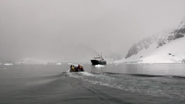 Ship and people in rubber boat on background of ice in ocean of Antarctica.