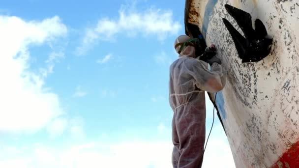 Workers tear off paint on metal in repairs process at shipyard.