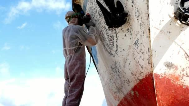 Dělníci odtrhnout nátěr na kov v procesu opravy v loděnici