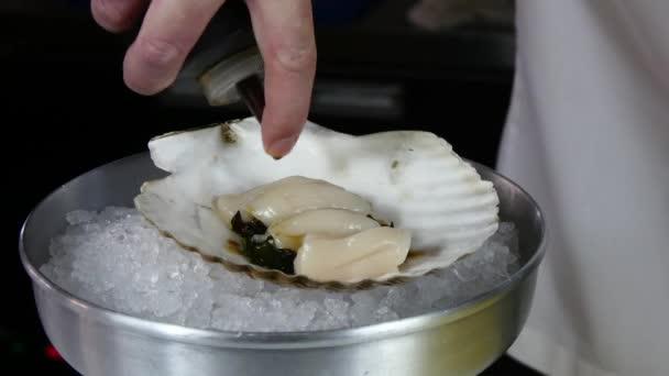 Kuchař připravuje moře salát mušle na shell.