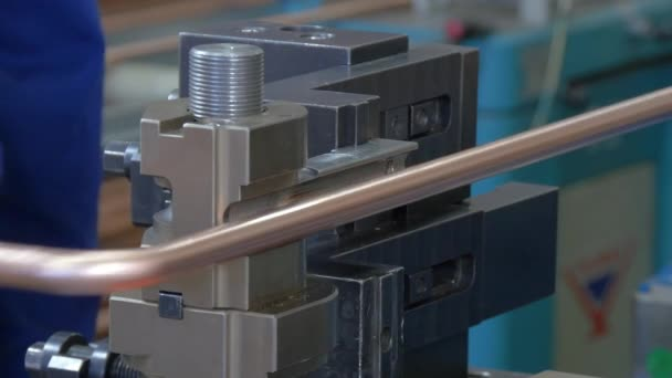 Bending of metal tubes on industrial machine in factory.