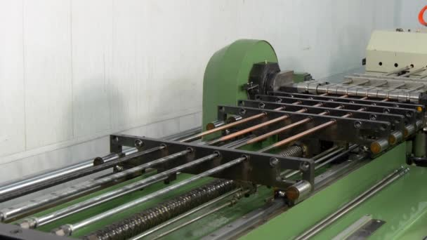 Bending and cutting metal copper pipes tubes on industrial CNC machine.