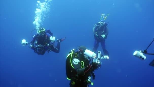 Group of diver and movie camera operator make a video undwewater.
