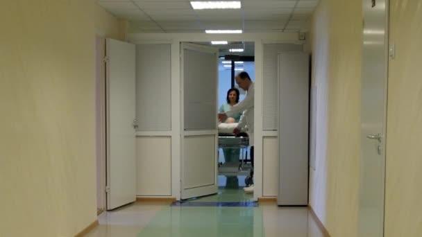 Lékař a zdravotní sestra pacient kolečka na kočárek na operačním sále v nemocnici