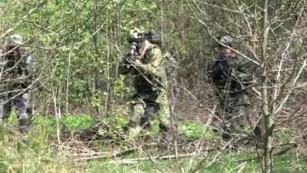 People in uniform on background of military hand grenade explosion in forest.