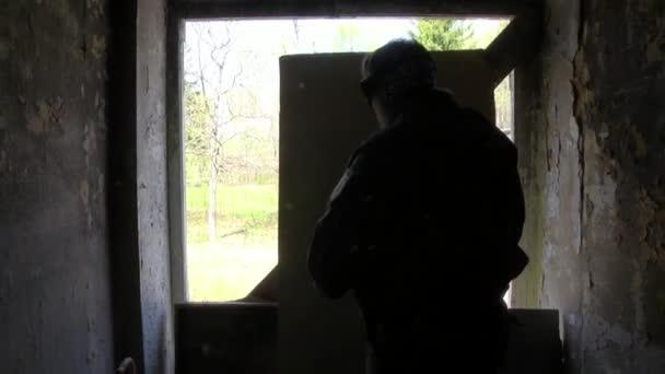 Spieler von Airsoft in Militäruniform mit Waffe ist in Lage in der Nähe eines Fensters in ein verfallenes Haus.