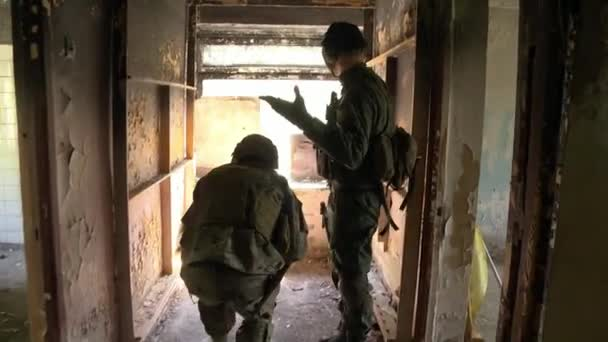 Soldat in Militäruniform mit Waffe auf Hintergrund der Hausruine ausgeführt.