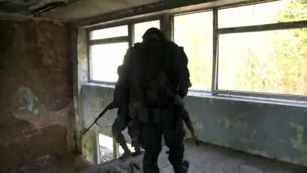 Soldiers in military uniform with weapon walk by the destroyed house