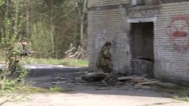 Soldaten in Militäruniform mit Waffe laufen auf Hintergrund der Hausruine.
