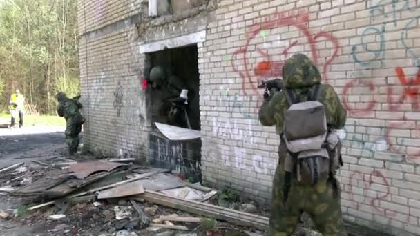 Soldaten in Militäruniform mit Waffe gehen auf Grund der Hausruine.