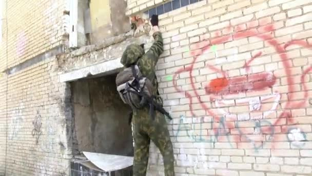 Airsoft men in military uniform with a weapon climbs up the ruined house.