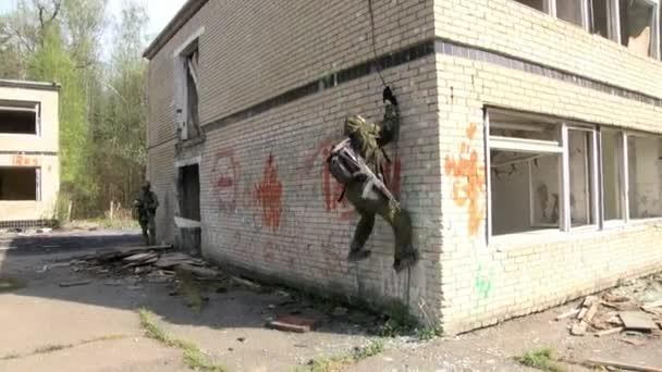 Airsoft-Männer in Militäruniform mit einer Waffe klettert die Hausruine.