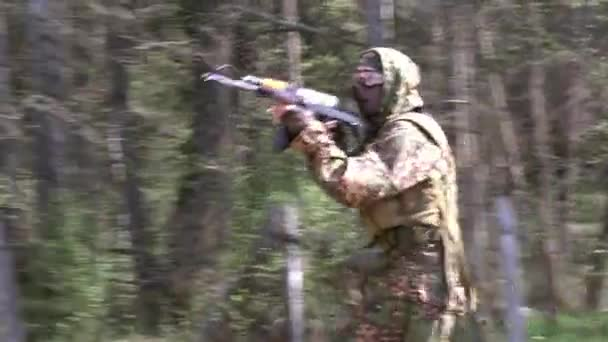 Soldier in military uniform with a weapon sneaks through the forest.