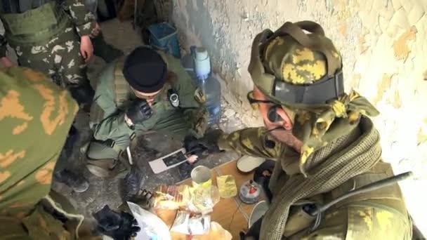 Menschen in Militäruniform mit Waffe sprechen im zerstörten Haus.