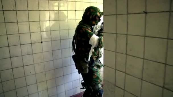 Soldat in Militäruniform mit einer Waffe versteckt in einem zerstörten Haus.