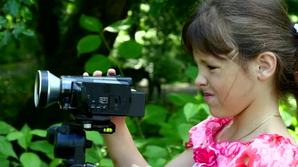 Young girl looks into video camera on background of green park background. Children outdoors in summer are creative work of cinema. Beautiful footage for family. Interesting world in childhood.