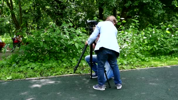 Two boys set video camera on a tripod of green park background.